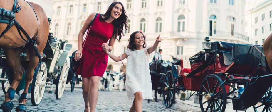 fröhliche Mutter mit kleiner Tochter in sommerlicher Kleidung vor Fiakern in Wien